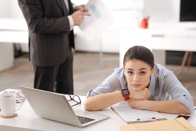 Moe kantoormedewerker haar voorhoofd rimpelen handen op de tafel zetten terwijl haar hoofd buigen