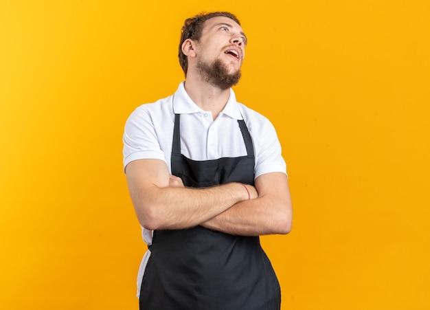 Moe kijken naar jonge mannelijke kapper met uniforme kruisende handen geïsoleerd op gele achtergrond