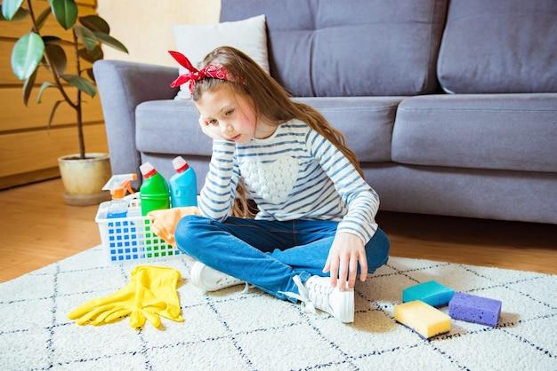 Moe kind meisje huisvrouw met reinigingsapparatuur zitten in de woonkamer. concept van het betrekken van kinderen bij huishoudelijk werk en schoonmaken