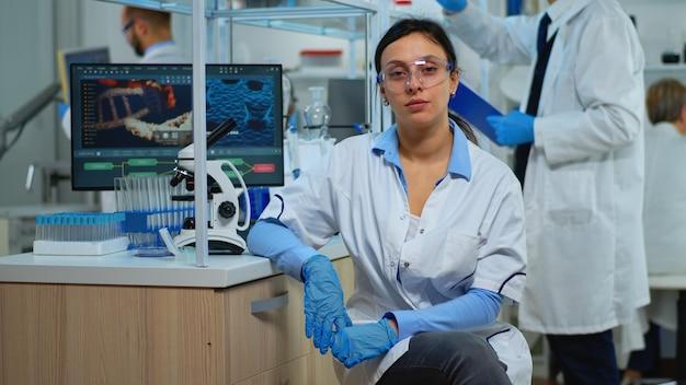 Moe laboratorium arts kijken camera glimlachend in modern uitgerust lab. multi-etnisch team dat virusevolutie onderzoekt met behulp van hightech- en scheikundige hulpmiddelen voor wetenschappelijk onderzoek, vaccinontwikkeling.