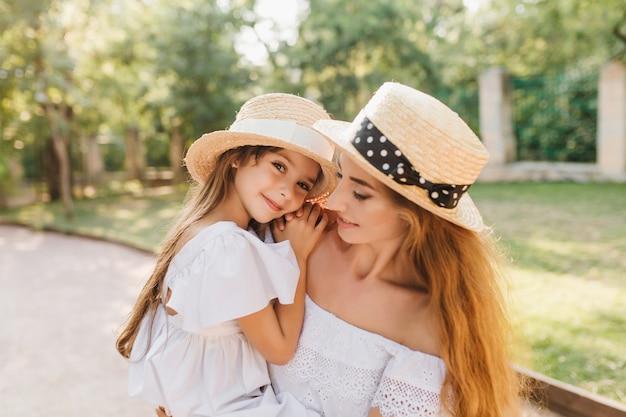 Moe lachende meisje in stro schipper rusten op moeders handen na een lange wandeling in het park. openluchtportret van blij mooie vrouw met dochter in witte jurk die zachtjes haar nek omhelst.