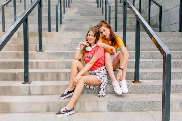 Moe maar tevreden brunette meisje in trendy witte sneakers ontspannen op stenen trappen met beste vriend