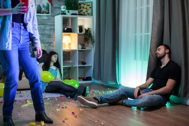 Moe man liggend op de vloer op het feest. groep mensen.
