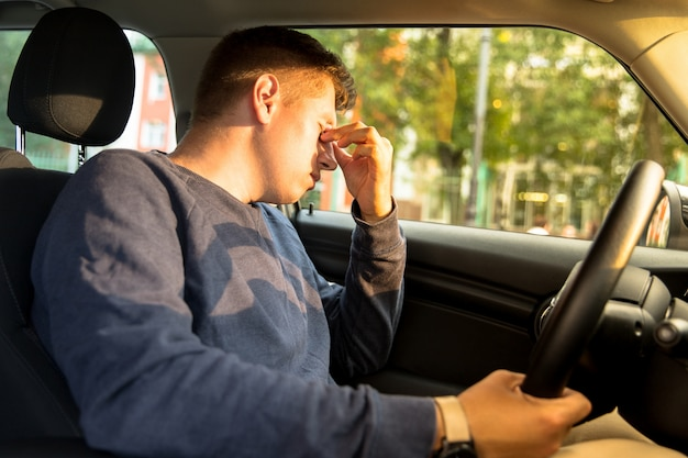 Moe man met hoofdpijn na het rijden. uitgeput, slaperig, overwerkt bestuurder