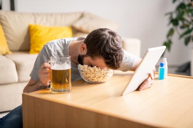 Moe man zit aan koffietafel en slapen in popcorn kom tijdens het kijken naar video op tablet thuis, isolatie periode concept