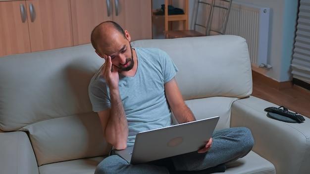 Moe man zittend op de bank tijdens een gesprek met een collega tijdens een zakelijke videocall-conferentie