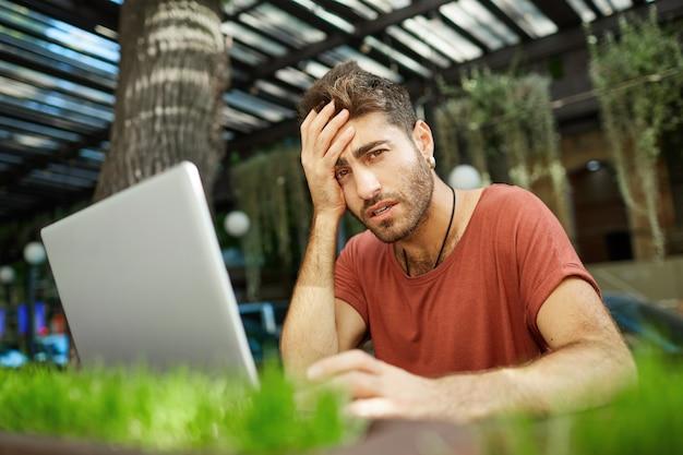 Moe mannelijke programmeur, it-man op zoek uitgeput, zittend met laptop terras