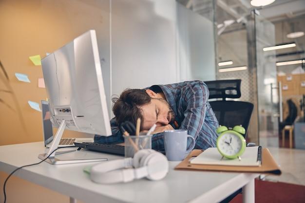 Moe mannelijke werknemer slapen aan tafel met computer, laptop, wekker en koptelefoon