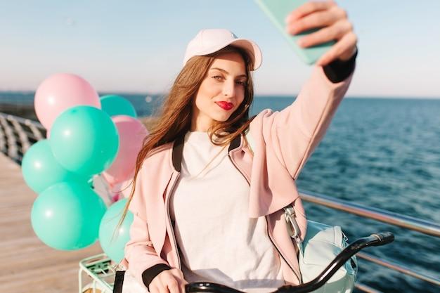Moe meisje met een stijlvolle make-up wordt gefotografeerd op de achtergrond van de zee na een fietstocht in de ochtend langs de pier.