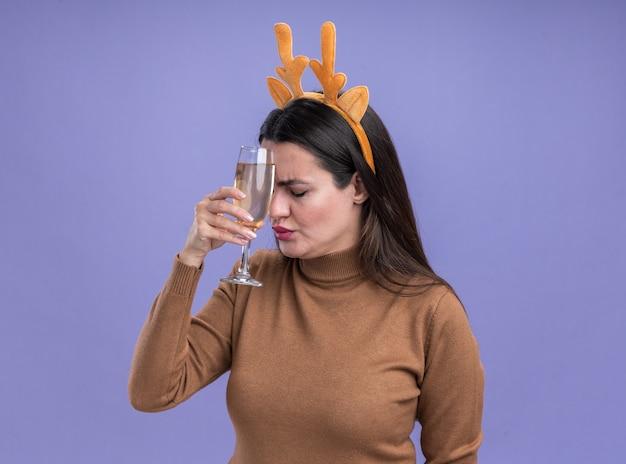 Moe met gesloten ogen jong mooi meisje draagt ?? bruine trui met kerst haar hoepel met glas champagne op voorhoofd geïsoleerd op blauwe achtergrond