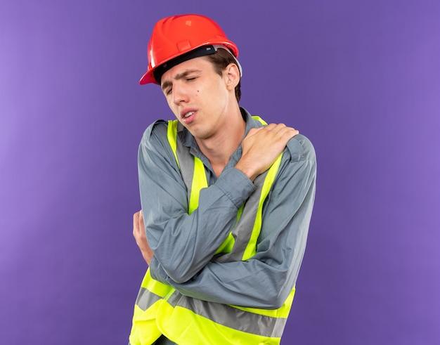 Moe met gesloten ogen jonge bouwer man in uniform hand op schouder zetten