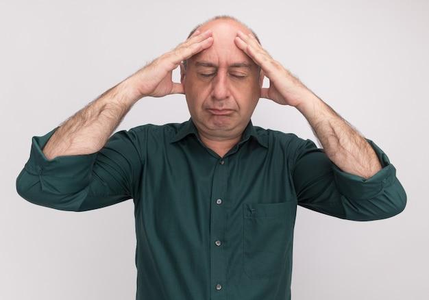 Moe met gesloten ogen man van middelbare leeftijd met groen t-shirt hand op voorhoofd zetten geïsoleerd op een witte muur