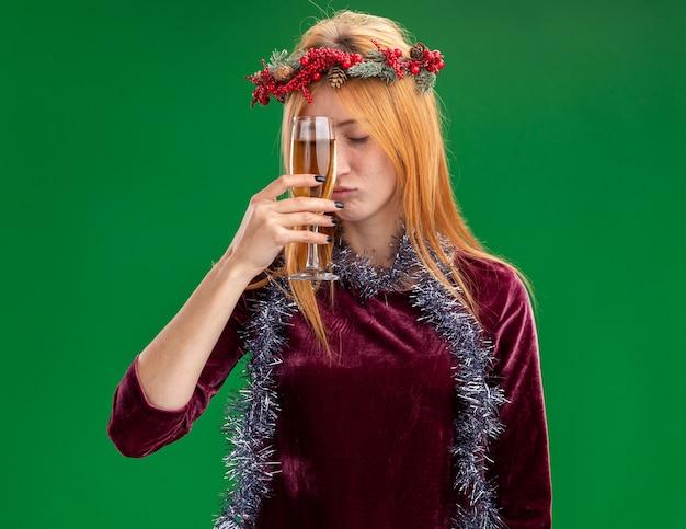 Moe met gesloten ogen mooi meisje dragen rode jurk met krans en garland op nek glas champagne rond voorhoofd geïsoleerd op groene achtergrond houden