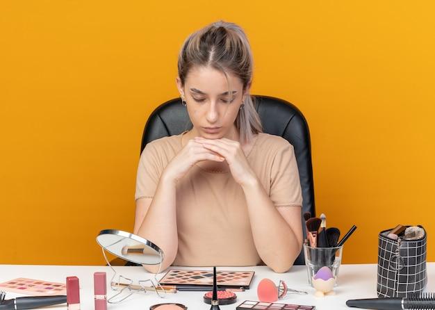 Moe met gesloten ogen zit jong mooi meisje aan tafel met make-up tools geïsoleerd op oranje achtergrond
