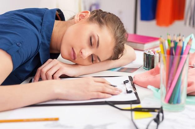 Moe modeontwerper. vermoeide modeontwerper slaapt op haar werkplek