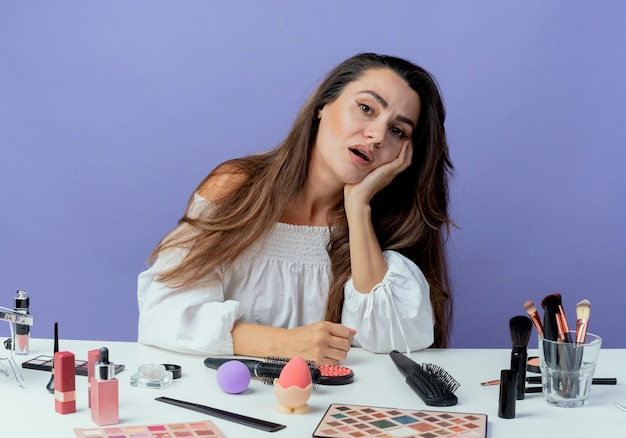Moe mooi meisje zit aan tafel met make-up tools legt hand op kin op zoek geïsoleerd op paarse muur