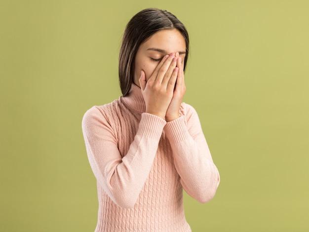Moe, mooi tienermeisje dat haar handen op het gezicht houdt met gesloten ogen, geïsoleerd op een olijfgroene muur met kopieerruimte
