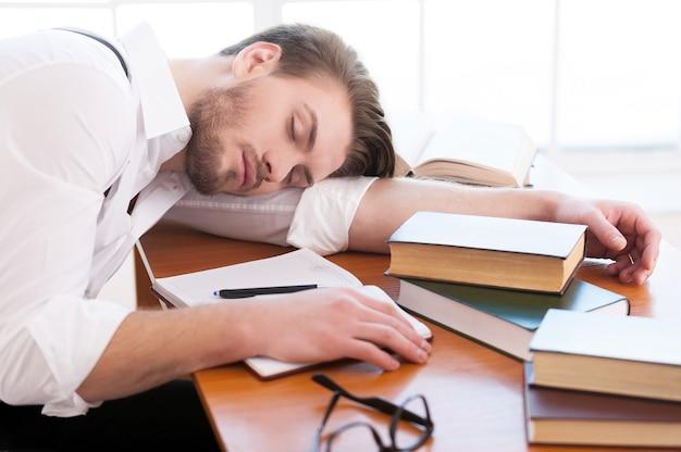 Moe na een nacht van onderzoek. achteraanzicht van een bedachtzame jongeman in hemd en bretels die op tafel zit en een boek leest dat erop ligt