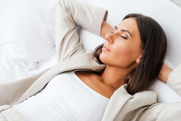 Moe na een zware werkdag. bovenaanzicht van mooie jonge zakenvrouw in pak die handen achter het hoofd houdt en de ogen gesloten houdt terwijl ze in bed in de hotelkamer ligt