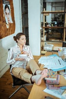 Moe na het werk zwangere succesvolle mooie vrouw die zich moe voelt na het werk wat wortelen te eten