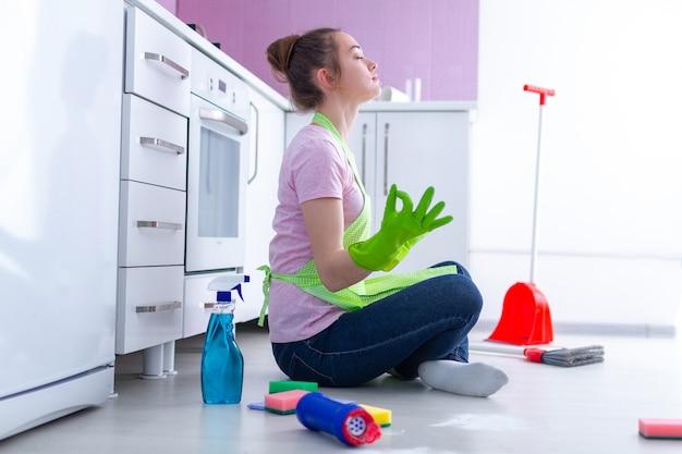 Moe overwerkte jonge huisvrouw die moeheid van een drukke dag voelen en ontspannen tijdens het schoonmaken van het huis en het huishouden in de keuken thuis