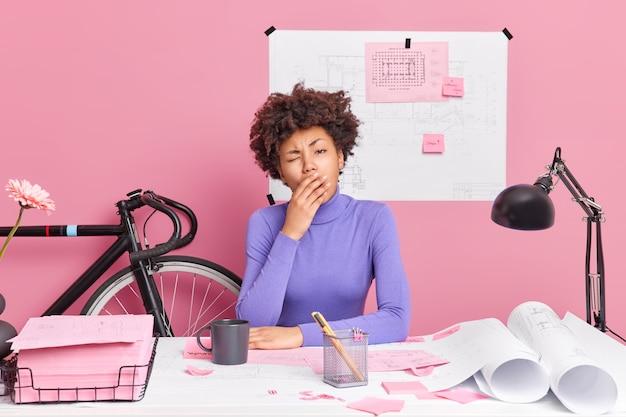 Moe overwerkte jonge vrouw met donkere huid gaapt en heeft slaperige uitdrukkingshoudingen op het bureaublad heeft deadline om projectwerk voor te bereiden voelt zich uitgeput door het voltooien van de taak