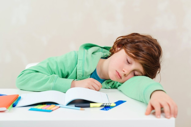 Moe schooljongen slapen aan tafel tijdens huiswerk. studieproblemen, onderwijs.