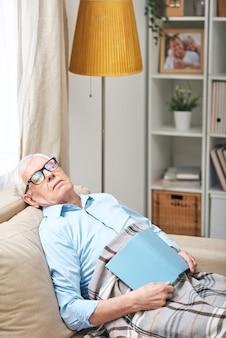 Moe senior man in glazen onder plaid op de bank zitten en slapen met boek in de woonkamer