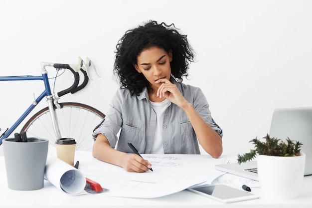 Moe serieuze jonge donkere vrouw ingenieur kijken naar haar tekening