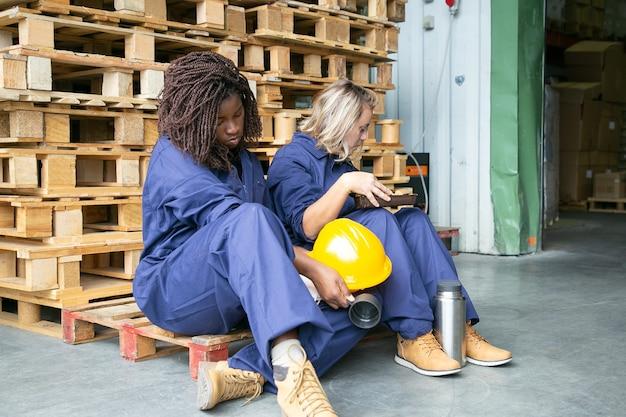 Moe slaperig diverse vrouwelijke fabrieksarbeiders zittend op houten pallets met thermoskan en koekjes