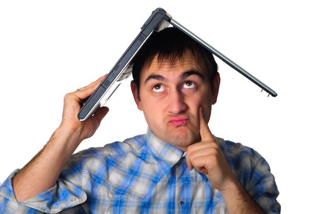 Moe, slaperige man houdt een laptop vast als een dak van een huis. geïsoleerd op wit. programmeur heeft een deadline.