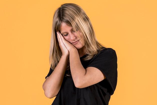 Moe slaperige vrouw neemt dutje leunen op haar palm voor gele achtergrond