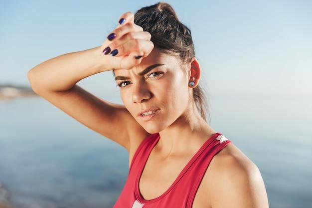 Moe sport vrouw ontspannen na de training en camera kijken