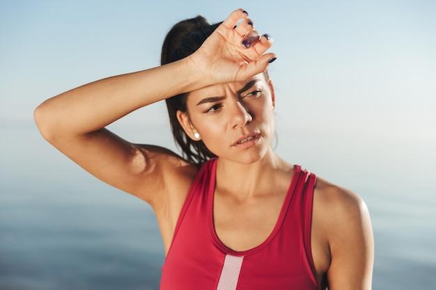 Moe sport vrouw ontspannen na de training en wegkijken