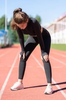 Moe sportieve fitness vrouw in sportkleding uitgeput ademhaling na het hardlopen op een loopband rubberen stadion
