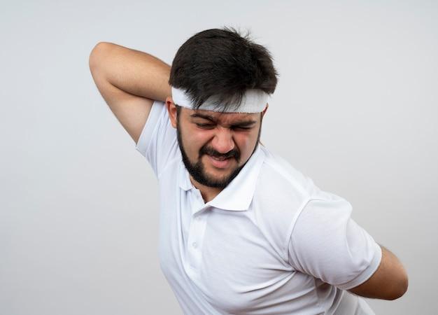Moe sportieve jongeman met gesloten ogen dragen hoofdband en polsband hand zetten taille geïsoleerd op een witte muur