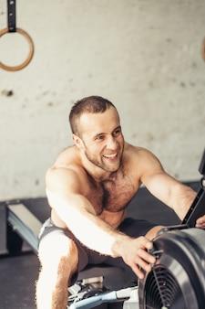 Moe sportieve mannelijke trainingen op kracht oefening machine in een sportschool club