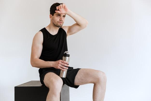 Moe sterke jonge sport man drinkwater geïsoleerd.