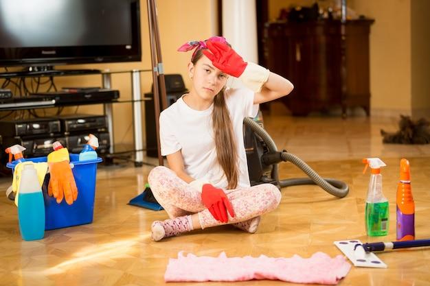 Moe tienermeisje zittend op de vloer na het schoonmaken van de woonkamer