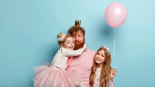 Moe triest alleenstaande vader organiseert echte vakantie voor kinderen, draagt kroon, ontvangt knuffel van kleine dochter, klein meisje met lang haar houdt luchtballon vast, glimlach staat gelukkig in de buurt. familiefeest