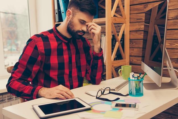 Moe trieste zakenman met hoofdpijn na werkdag