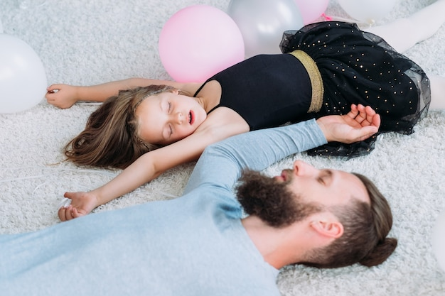 Moe uitgeput vader viel uit en viel in slaap met kleine hyperactieve dochter. vaderschap en zoete momenten uit de kindertijd.