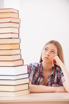 Moe van het studeren. depressief tienermeisje dat de hand op de kin houdt en naar de bovenkant van de grote stapel boeken kijkt die op het bureau liggen