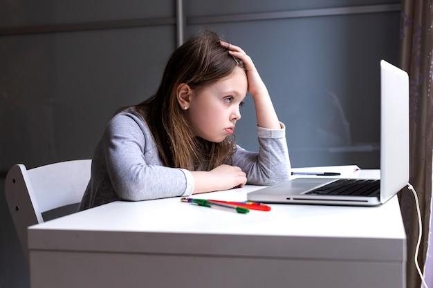 Moe van online computerlessen meisje kijkt thuis verdrietig naar de monitor