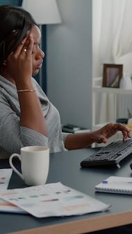 Moe, verontruste zwarte student die aan hoofdpijn lijdt, zittend aan een bureautafel in de woonkamer, op zoek naar medische behandeling met behulp van de computer. bezorgde zieke overstuur jonge vrouw met migrainepijn tijdens lockdown