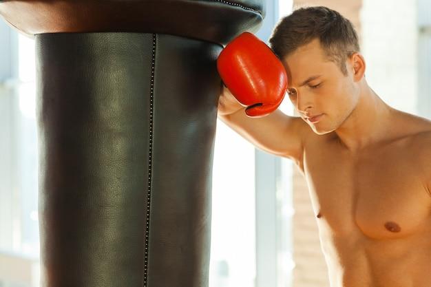 Moe voelen na de training. moe jonge bokser in sporthandschoenen leunend op de bokszak Premium Foto