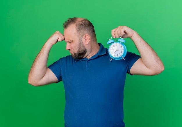 Moe volwassen slavische man met wekker draaien hoofd zetten vuist op voorhoofd met gesloten ogen geïsoleerd op groene muur