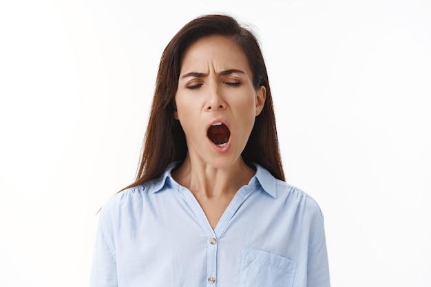 Moe volwassen vrouw hardwerkende zakenvrouw laat op het werk blijven, moe gapen, ogen sluiten, mond wijd openen, zich slaperig voelen uitgeput, willen slapen, vroeg in de ochtend wakker worden, op een witte muur staan