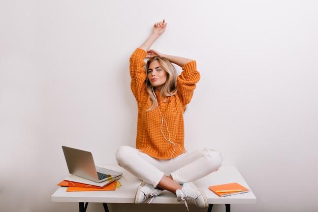 Moe vrouw in witte lederen sneakers die zich uitstrekt na een zware dag, zittend op tafel