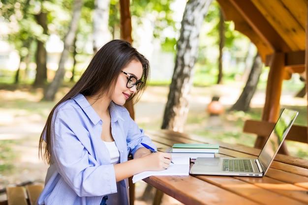 Moe vrouw met behulp van een laptop in een parktafel aan het eind van de dag